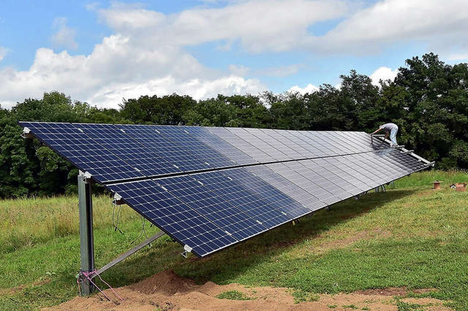 In this Aug. 12, 2016 photo, Rob Mathis working for CH Electrical installs a panel on a bank of solar panels at Blue Sky Vineyard, in Makanda, Ill. The Madison County Zoning Board of Appeals approved a second pair of solar farms, this pair in Edwardsville, on Tuesday. Previously, a solar farm near St. Jacob was approved by the full Madison County Board last week. Photo: Richard Sitler /The Southern, Via AP