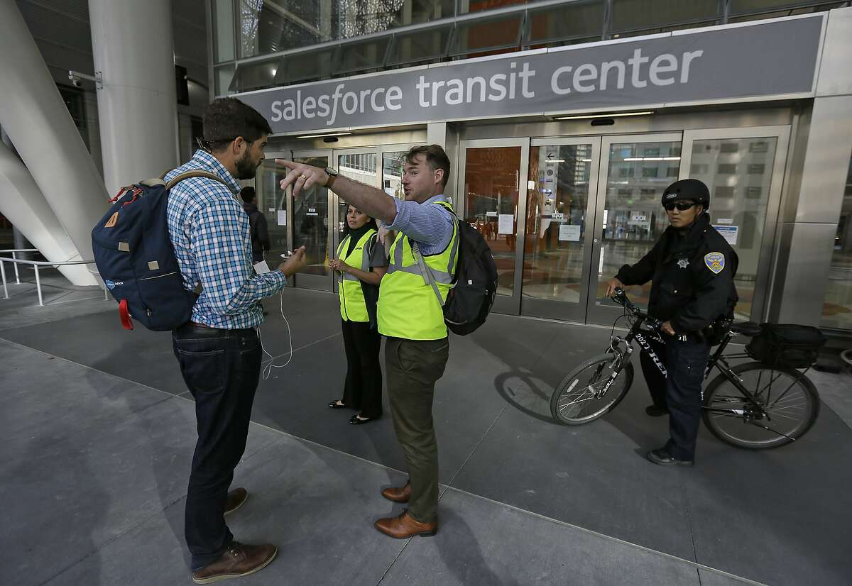 """Mike Eshleman, with AC Transit, directs people away from the Salesforce Transit Center following its closure, Tuesday, Sept. 25, 2018, in San Francisco. San Francisco officials shut down the city's celebrated new $2.2 billion transit terminal Tuesday after discovering a crack in a support beam under the center's public roof garden. Coined the """"Grand Central of the West,"""" the Salesforce Transit Center opened in August near the heart of downtown after nearly a decade of construction. It was expected to accommodate 100,000 passengers each weekday, and up to 45 million people a year. (AP Photo/Eric Risberg)"""