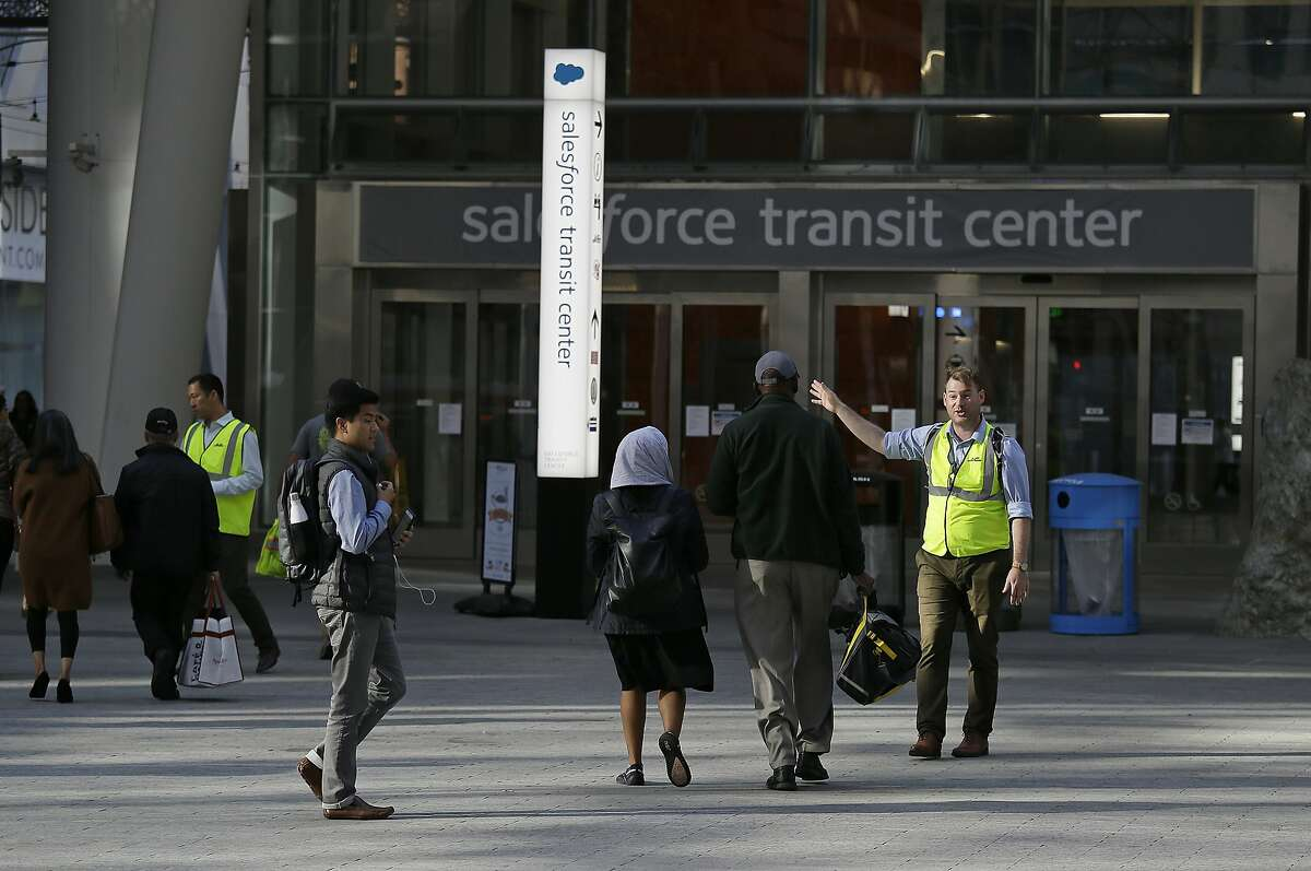 """People are directed around the Salesforce Transit Center following its closure Tuesday, Sept. 25, 2018, in San Francisco. San Francisco officials shut down the city's celebrated new $2.2 billion transit terminal Tuesday after discovering a crack in a support beam under the center's public roof garden. Coined the """"Grand Central of the West,"""" the Salesforce Transit Center opened in August near the heart of downtown after nearly a decade of construction. It was expected to accommodate 100,000 passengers each weekday, and up to 45 million people a year. (AP Photo/Eric Risberg)"""