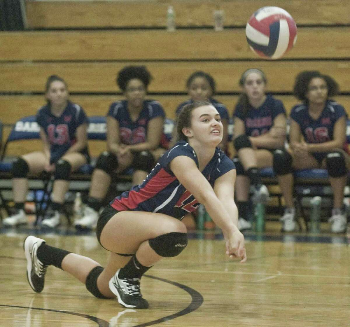 Brien McMahon High School's MaryAlice Smith digs out the ball in a game against Darien High School, played at Darien. Wednesday, Sept. 26, 2018