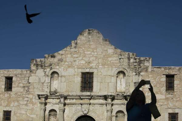 """A tourist takes a """"selfie"""" in front of the Alamo in April 2015."""