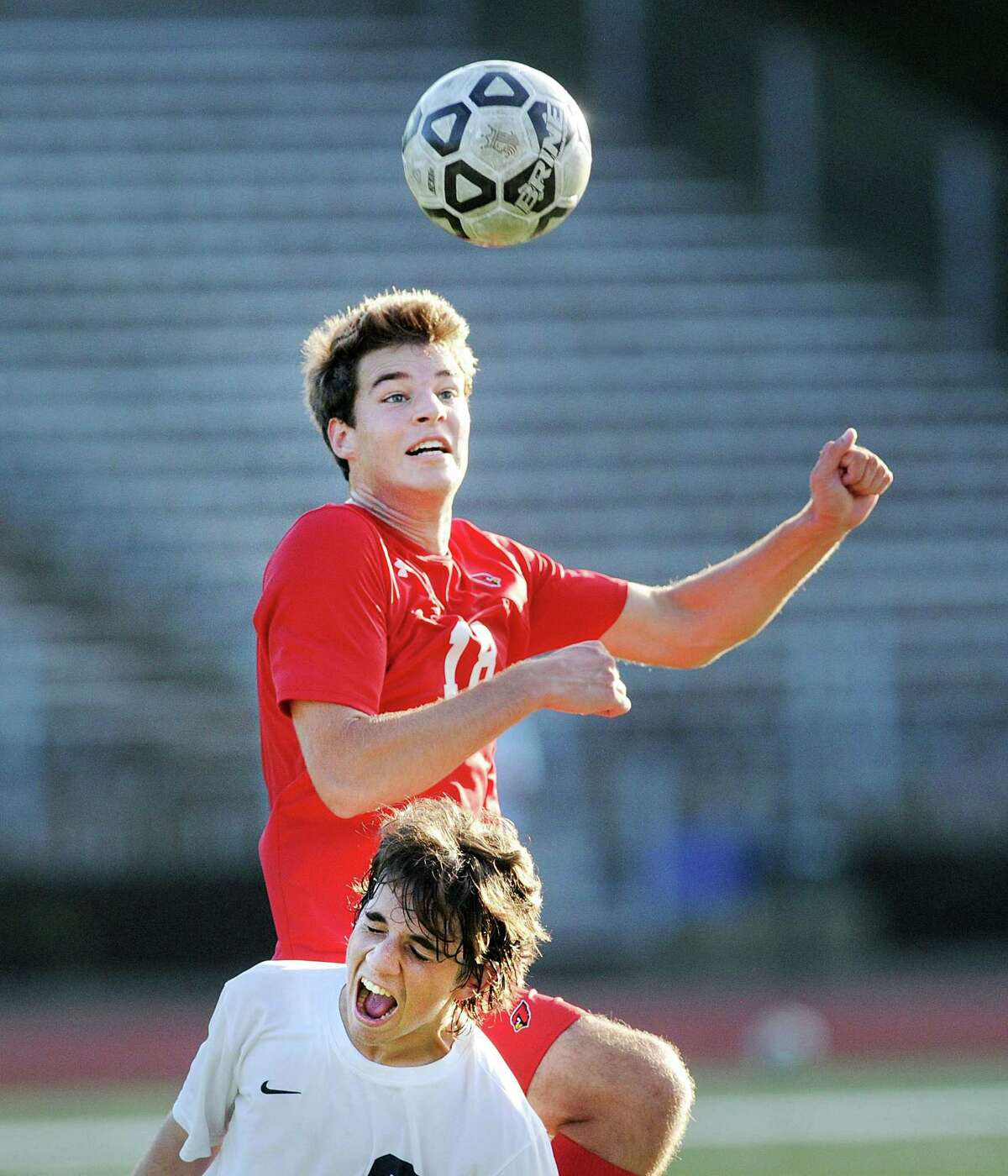 Dan Bourgeois of Greenwich, top, goes high above a Staples defender to head the ball during the boys high school soccer match between Greenwich High School and Staples High School at Greenwich, Conn., Wednesday, Sept. 26, 2018.