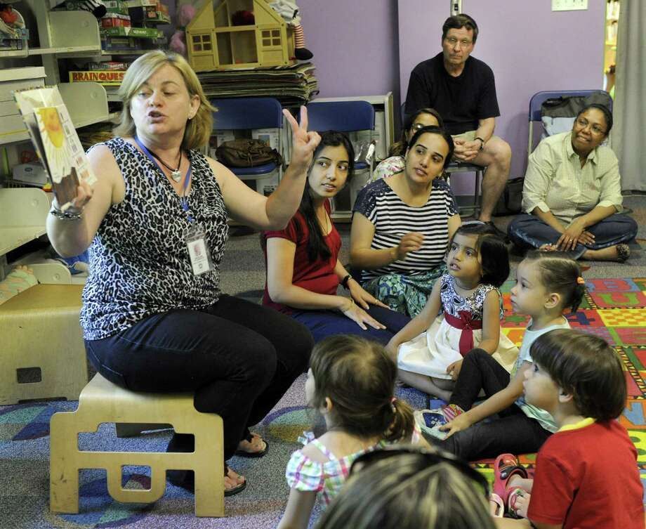 Angelina Stojakovic, parent educator at the Danbury Learning Center, reads a book, during a weekly class offered by The United Way of Western Connecticut, Wednesday, June 10. The class, held at the Danbury Library, is a pilot program for the largely-Latino neighborhood around the Park Avenue Elementary School to teach parents how to be the primary educators of their children. Photo: Carol Kaliff / Hearst Connecticut Media / The News-Times