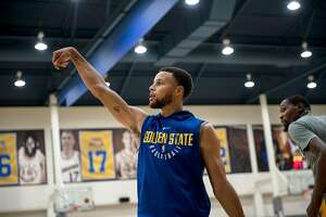 Stephen Curry watches his shot as he and Kevin Durant, right, shoot around during a practice at the Golden State Warriors Rakuten Center in Oakland, Calif., on Wednesday September 26, 2018
