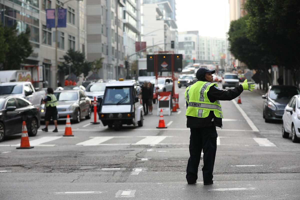 A SFMTA traffic enforcement officer directs traffic at Fremont and Howard near the Transbay Transit Center.