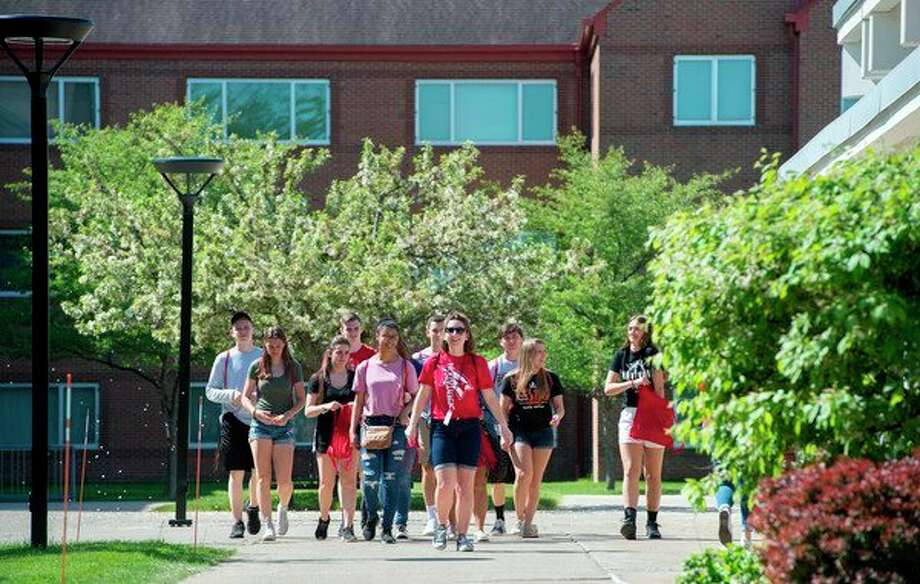 Allie Roggenbuck, a communication major from Harbor Beach and Orientation leader (red shirt, center), leads a group of incoming freshmen on a campus tour of Saginaw Valley State University as part of the new students' orientation program. (Photo provided/Michael Randolph, SVSU)