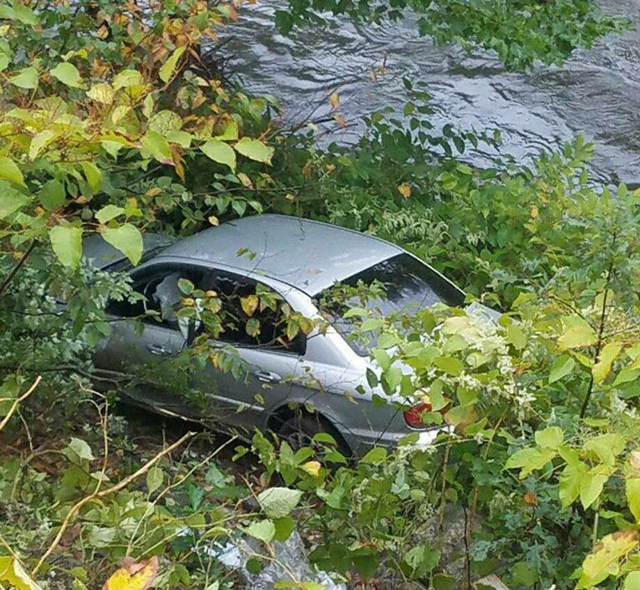 Two vehicles came with a few feet of the rain-swollen Naugatuck River after traveling off Route 8 on Wednesday, Sept. 26, 2018. State Police said the two-vehicle crash happened on southbound Route 8 in Beacon Falls. There were no injuries. Photo: State Police Photo