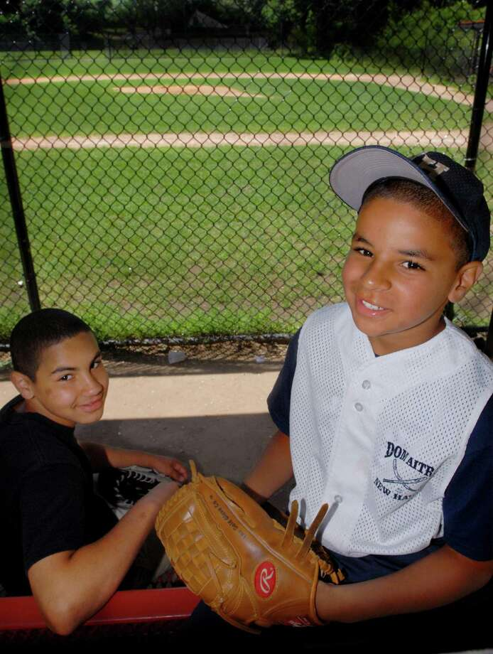 Jericho Scott, right, with his brother, at Dom Aitro Little League Field in New Haven. Scott was fatally shot shortly after midnight on April 19, 2015. He was seated in a vehicle parked on Exchange Street near his home in New Haven. Two other individuals standing near the vehicle were wounded in the same incident. The shootings are believed to have been in retaliation for an alleged robbery that occurred days before, but police do not believe Jericho was the intended target. Photo: Melanie Stengel / New Haven Register