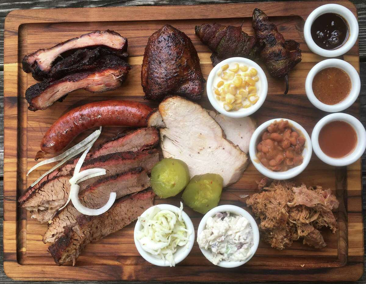 The Two Bros. BBQ Market board includes (from top left): cherry-glazed babyback pork ribs, chicken thigh, jalapeño poppers, creamed corn, beans, pulled pork, potato salad, smoked turkey, coleslaw, brisket and sausage.