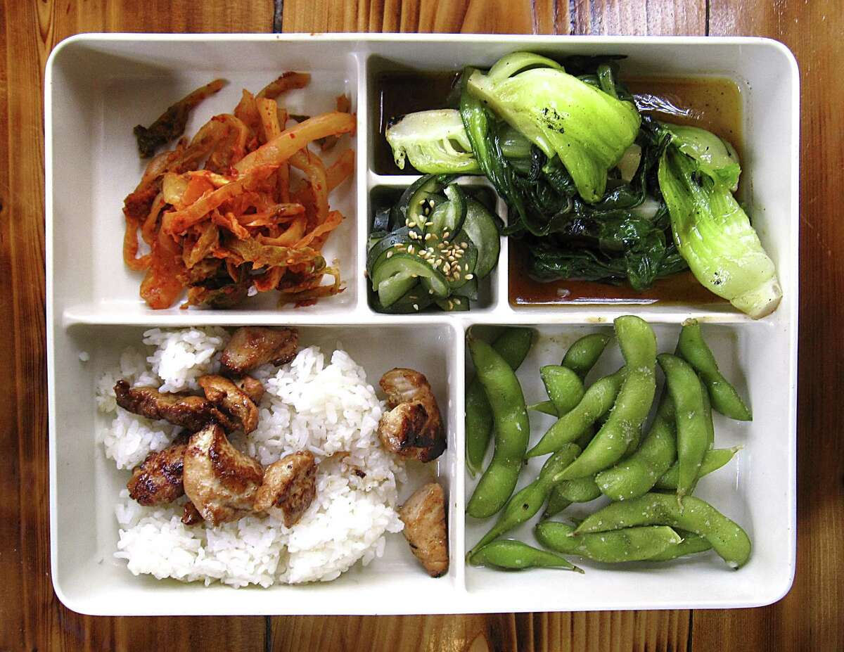 Bento box with kimchi, pickles, grilled bok choy, edamame and grilled chicken with rice from Kimura.