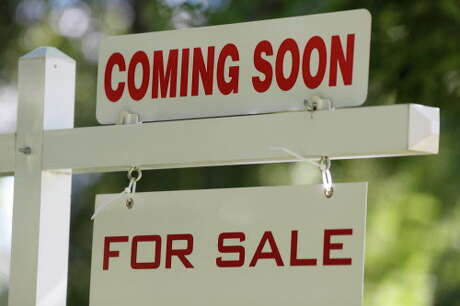 In this Thursday, Aug. 30, 2018, photograph, a sale signs stand outside a home on the market in Denver. (AP Photo/David Zalubowski)