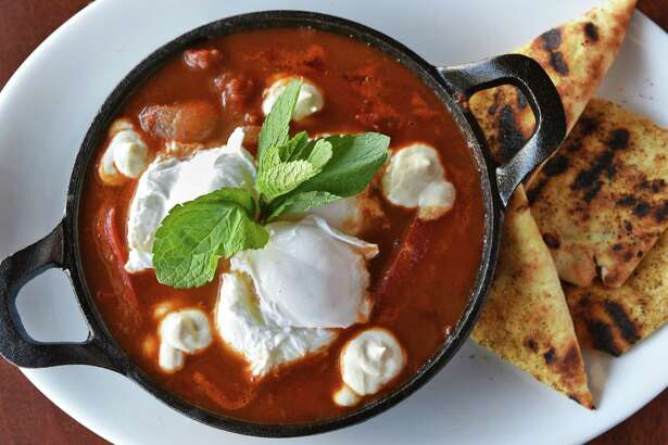 Shakshuka (eggs in spiced tomato sauce) and flatbread with Zatar spice at the New World Bistro Bar Wednesday March 22, 2017 in Albany, NY. (John Carl D'Annibale / Times Union)