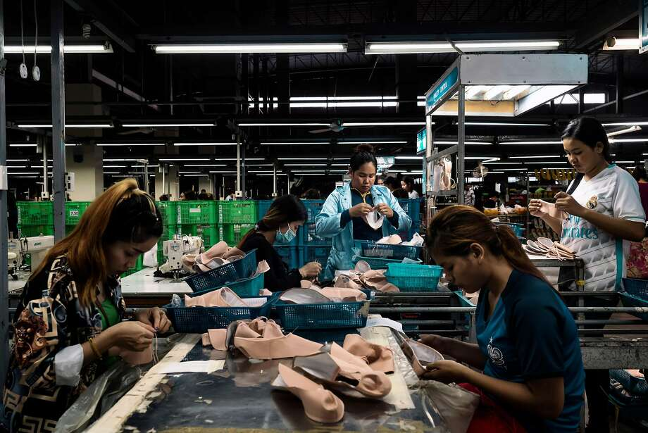 Workers making Bloch ballet shoes cut leather from Brazil, apply glue and mold the material into soles in Cambodia. Photo: Adam Dean / New York Times