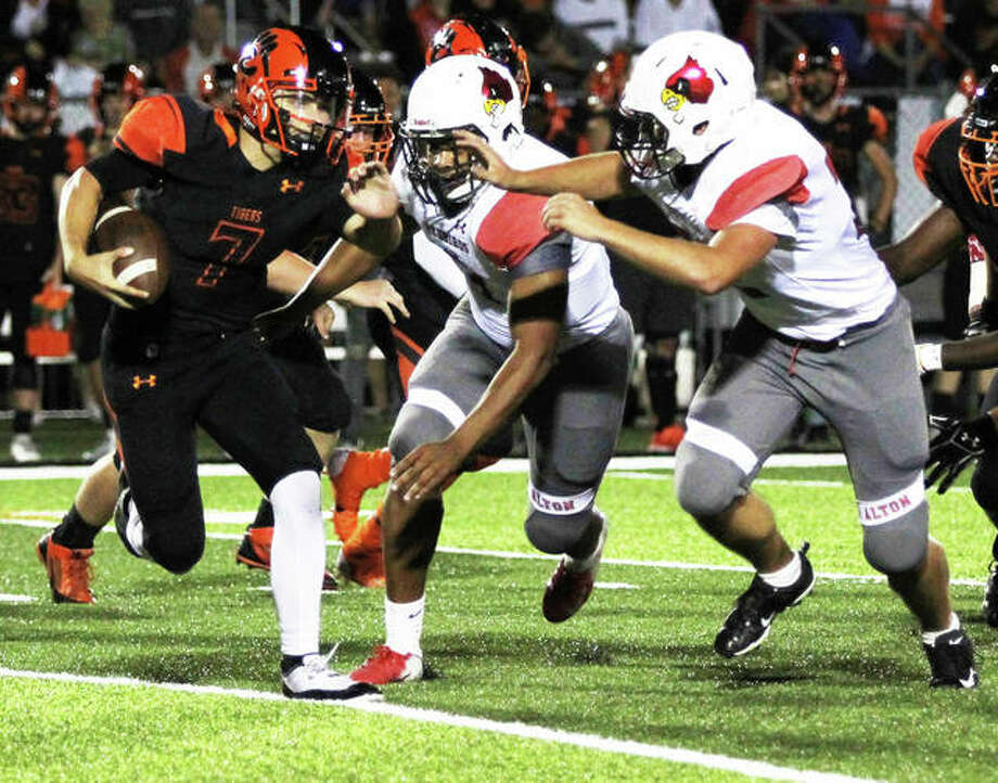 Edwardsville QB Luke Oglesby (7) can't escape pressure from Alton's Izeal Terrell (middle) and Tristan Underwood (right) during the first half Friday night at the District 7 Sports Complex in Edwardsville. Photo: Greg Shashack / The Telegraph
