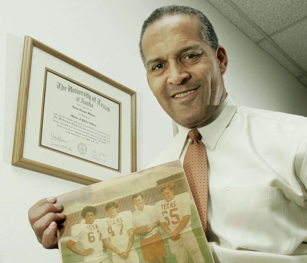 Dallas attorney and former Texas Longhorn Julius Whittier holds a newspaper clipping from 1971 featuring Whittier with teammates Bruce Cannon, Greg Dahlberg, and coach Darrell Royal. Whittier, the first African-American to letter in football at Texas, died Tuesday at age 68.