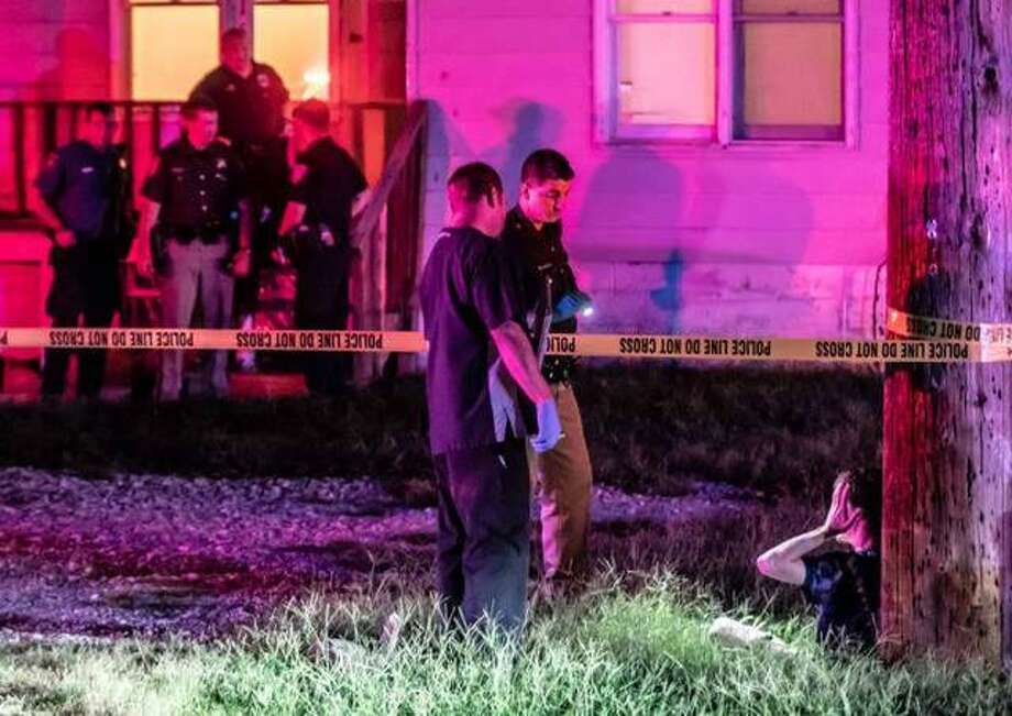 In this Aug. 16 file photo, a Madison County Sheriff's deputy and a paramedic speak to an unidentified man leaning against a utility pole at the scene of a shooting at 152 S. Oak St. in Cottage Hills that killed 24-year-old Damian M. Huber. Photo: Nathan Woodside | Telegraph File Photo