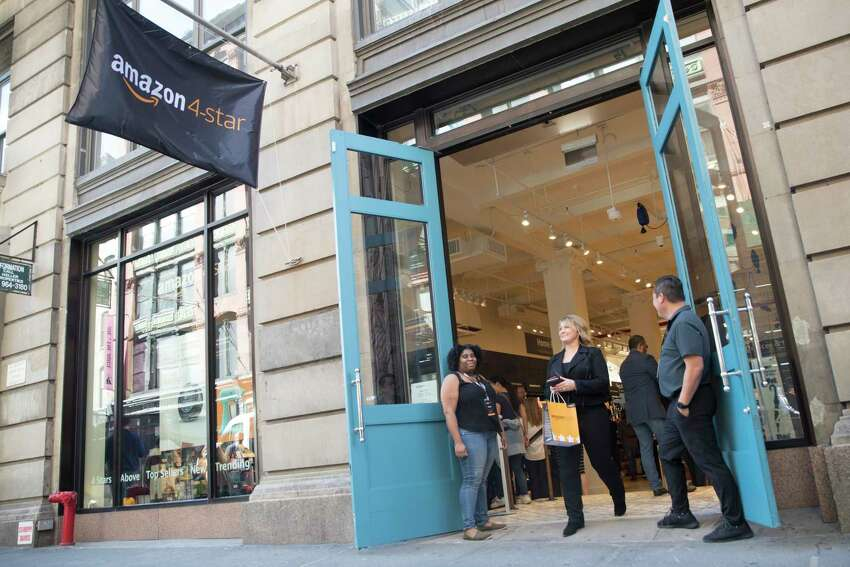 A shopper leaves the Amazon 4-star store in the Soho neighborhood of Manhattan after making a purchase, Thursday, Sept. 27, 2018. Amazon is expanding its physical presence again, this time opening a 4,000-square-foot store that sells a wide range of products, including shower curtains, Hallmark cards and baby bottles. (AP Photo/Mary Altaffer)