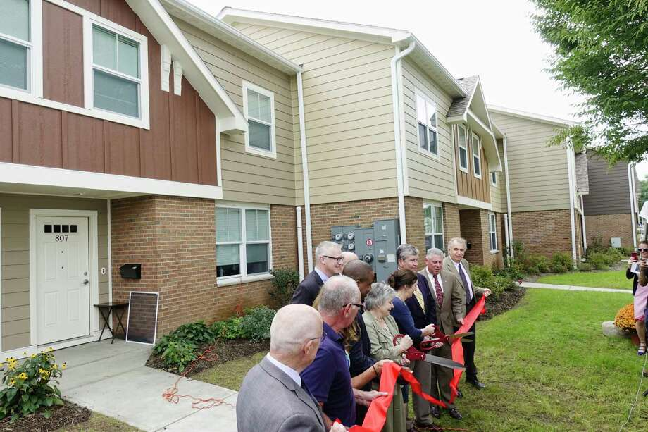 Elected officials and members of the Troy Housing Board of Commissioners take part in a ribbon cutting during an event to mark the completion of phase one of the $13 Million rehabilitation project at the Martin Luther King Apartments on Wednesday, Sept. 26, 2018, in Troy, N.Y. The project will be completed in the second phase.  (Paul Buckowski/Times Union) Photo: Paul Buckowski / (Paul Buckowski/Times Union)