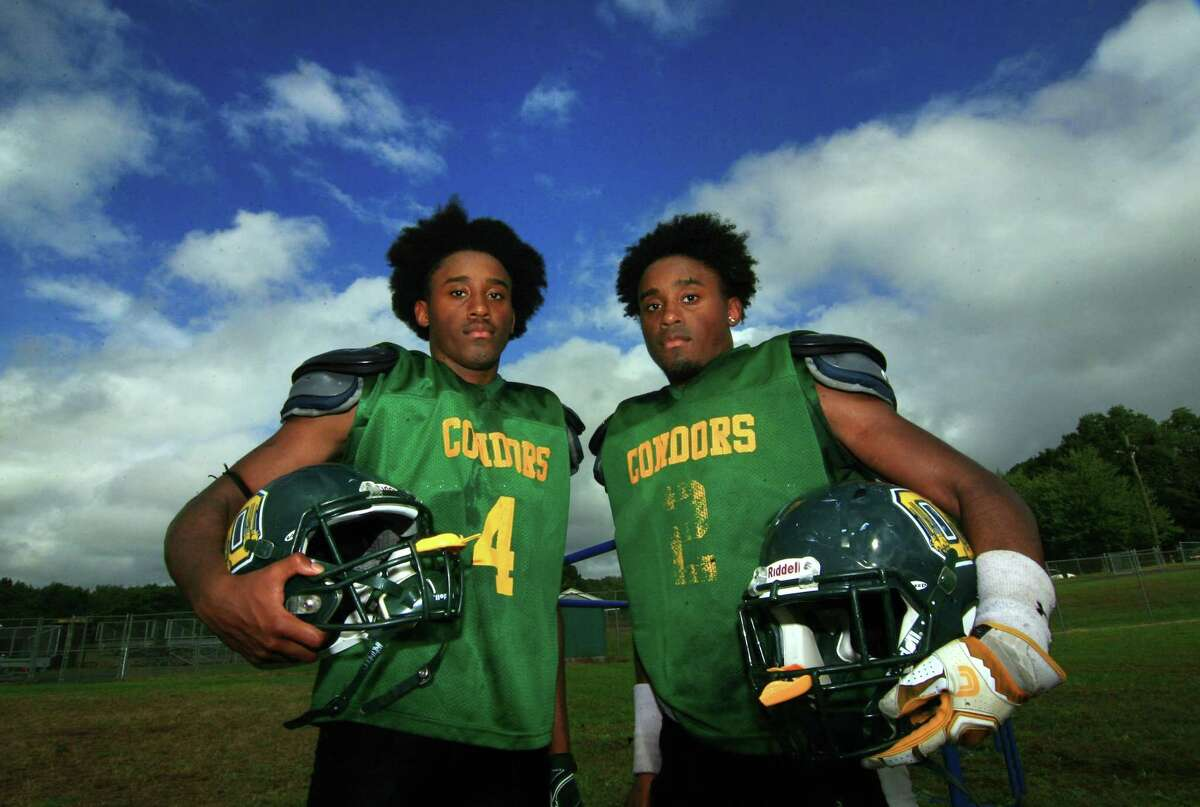 Emmett O'Brien Tech football stars and twin brothers Jonte Roc (4) and Jommar Roc (2) pose during high school football practice in Ansonia, Conn., on Wednesday Sept. 26, 2018.