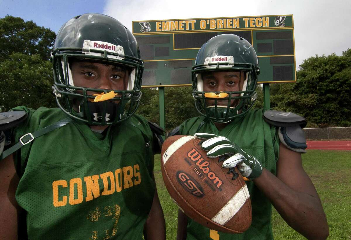 Emmett O'Brien Tech football stars and twin brothers Jommar Roc, left, and Jonte Roc pose during high school football practice in Ansonia, Conn., on Wednesday Sept. 26, 2018.