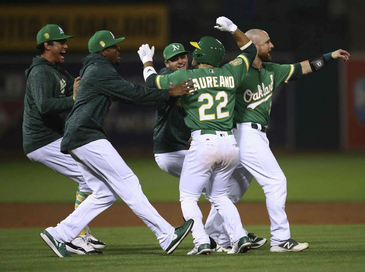 Oakland Athletics' Ramon Laureano (22) celebrates after making the game winning hit against the Detroit Tigers in the 13th inning of a baseball game Friday, Aug. 3, 2018, in Oakland, Calif. (AP Photo/Ben Margot)