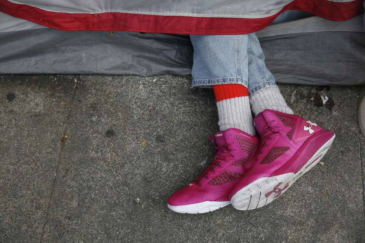 A person's sneakered feet stick out from a tent along 5th Street on Friday, May 25, 2018 in San Francisco, Calif.