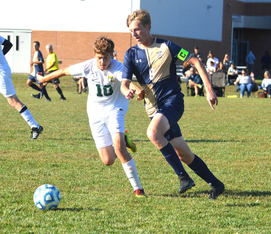 Metro-East Lutheran junior Owen Peterson, left, and Father McGivney junior Jonah Mitan chase down the ball during Thursday's game at FMCHS. Photo: Scott Marion