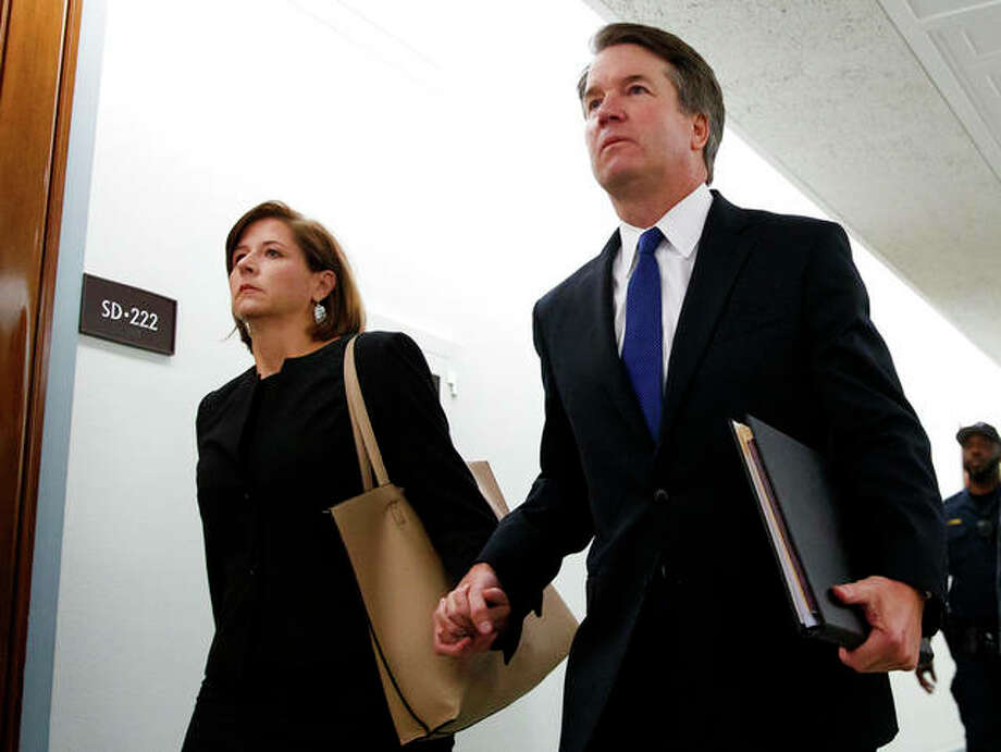 Brett Kavanaugh, President Donald Trump's Supreme Court nominee, and his wife, Ashley Estes Kavanaugh, hold hands as they arrive for a Senate Judiciary Committee hearing on Capitol Hill in Washington on Thursday. Carolyn Kaster | AP