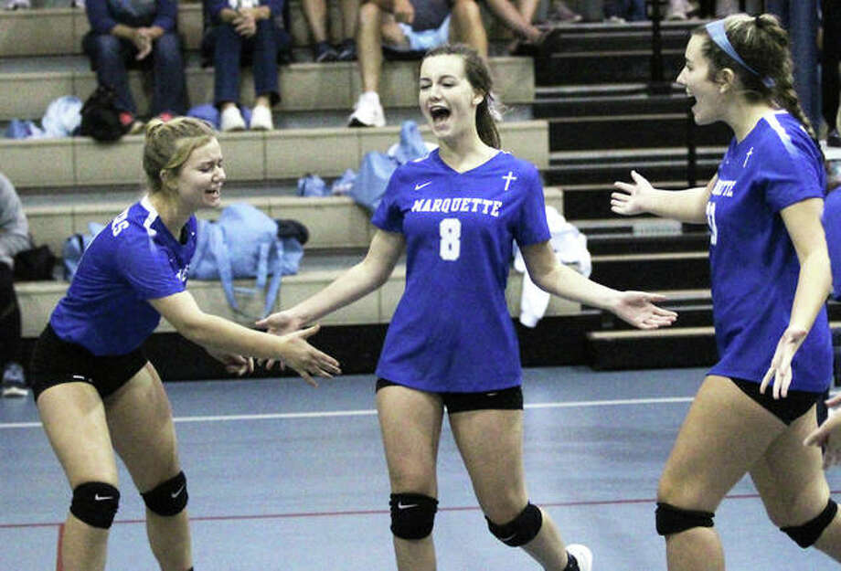 Marquette Catholic's Grace Nicholson (middle) celebrates a point earlier this season with teammates Josey Wahl (left) and Jenna Zacha (right). The Explorers beat Brussels in two sets Thursday night in Alton. Photo: Greg Shashack / The Telegraph