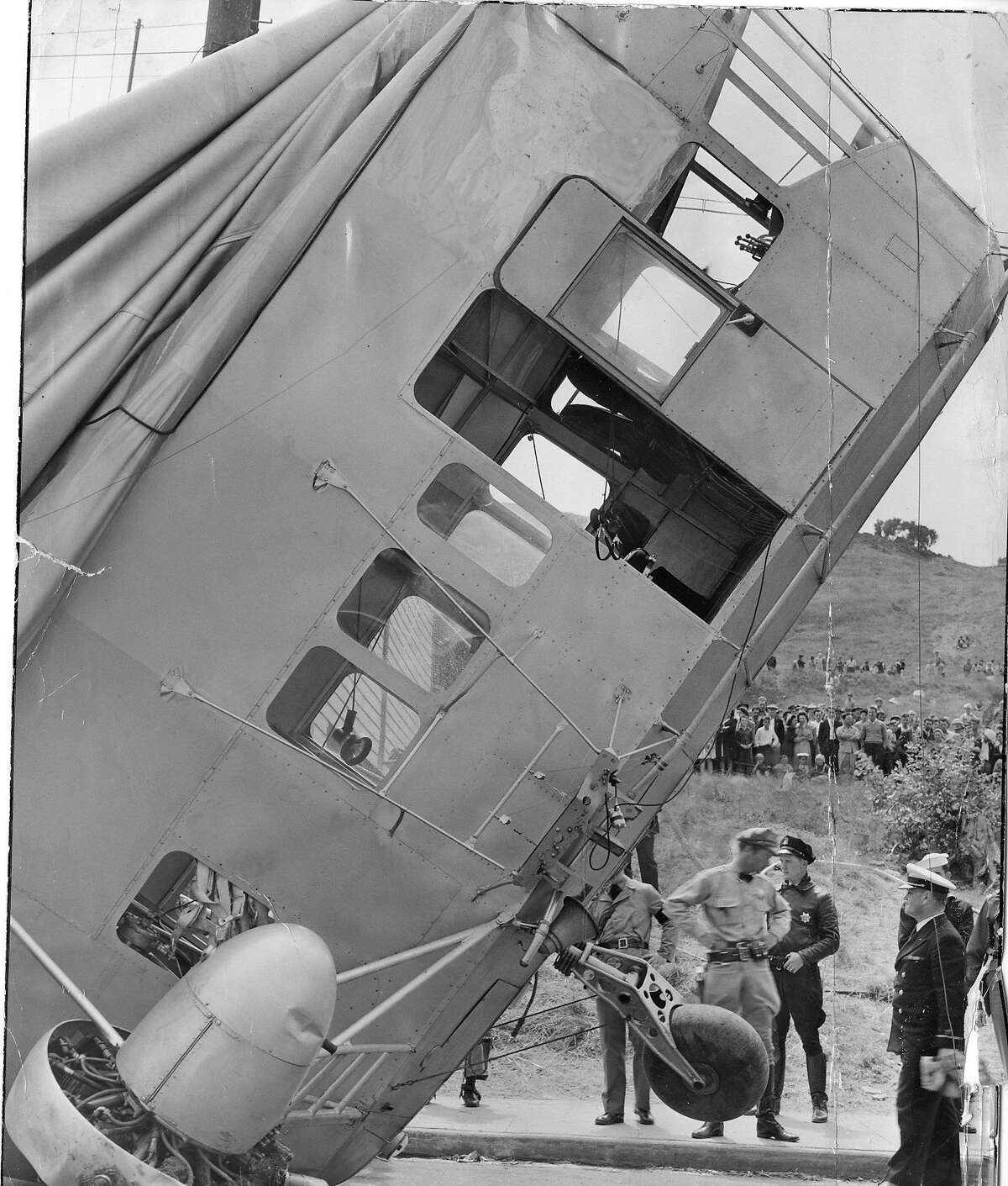 The gondola leans against a telephone pole as a crewless out of control Navy Patrol Blimp landed in a street in Daly City, August 16, 1942 U.S. Nay photo Photo ran 08/17/1942, P. 3