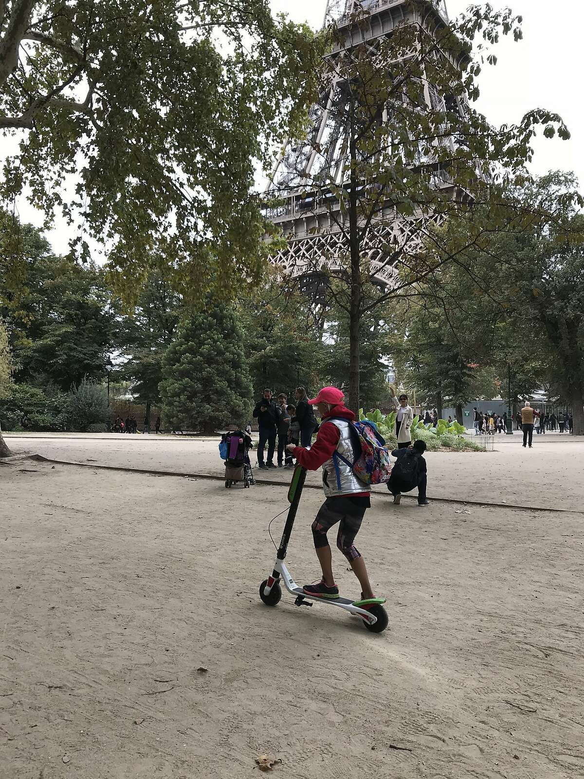 British tourist Sarah Westley rides a Lime scooter past the Eiffel Tower.