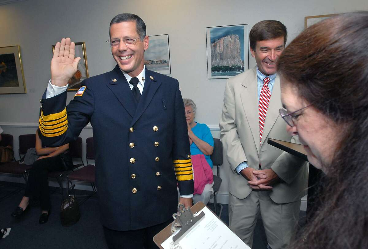 David Berardesca (left) is sworn in as the new Hamden Fire Chief by town clerk Vera Morrison (far right) at the Hamden Government Center on 8/15/2006. At right in back is Hamden Mayor Craig Henrici.
