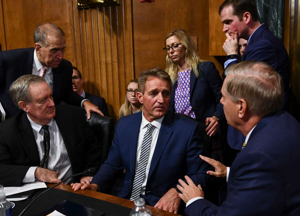 Senate Judiciary Committee member Senator Jeff Flake (R-AZ) (C) speaks with colleagues after a hearing on Capitol Hill in Washington, DC on September 28, 2018, on the nomination of Brett M. Kavanaugh to be an associate justice of the Supreme Court of the United States. - Kavanaugh's contentious Supreme Court nomination will be put to an initial vote Friday, the day after a dramatic Senate hearing saw the judge furiously fight back against sexual assault allegations recounted in harrowing detail by his accuser. (Photo by Brendan Smialowski / AFP) (Photo credit should read BRENDAN SMIALOWSKI/AFP/Getty Images)