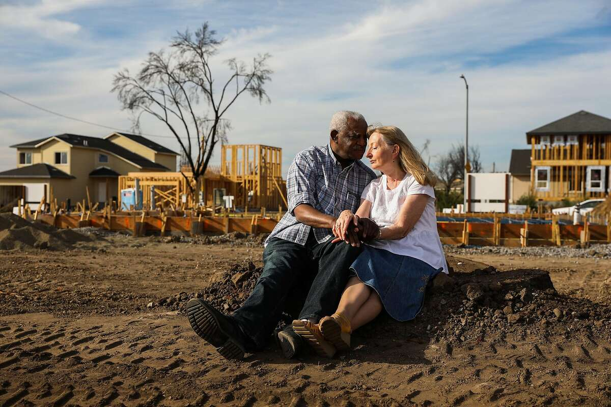 Husband and wife Henry Granger and Astrid Granger sit for a portrait on the stump of the Redwood tree that used to be part of their backyard before the Tubbs Fire destroyed their home in Santa Rosa, California, on Thursday, Sept. 27, 2018.
