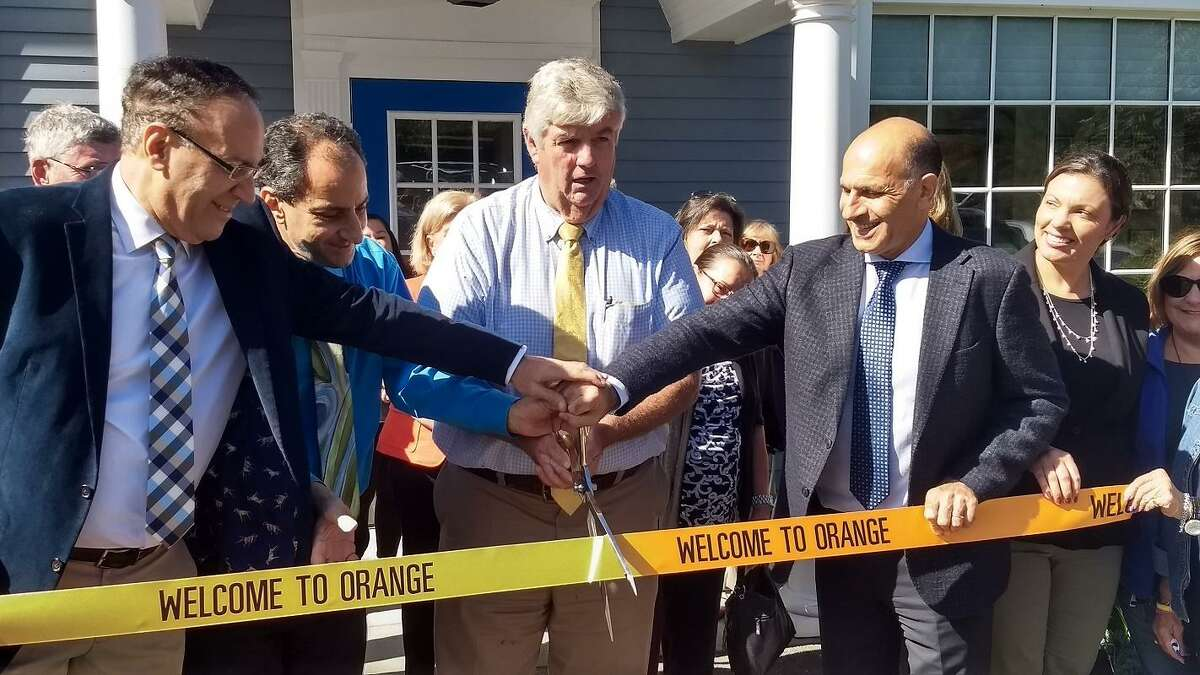 First Selectman Jim Zeoli prepares to cut the grand opening ribbon at Traveland, as the three brothers who own the agency smile on.