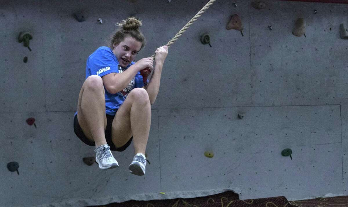"""Ryleigh Rodgers, 14, swings from a rope toward a black landing pad at Iron Sports Indoor Obstacle Course on Thursday, Spet. 27, 2018 in Houston. Rodgers competed in ?""""American Ninja Warrior Jr.?"""" which will air Oct. 13."""