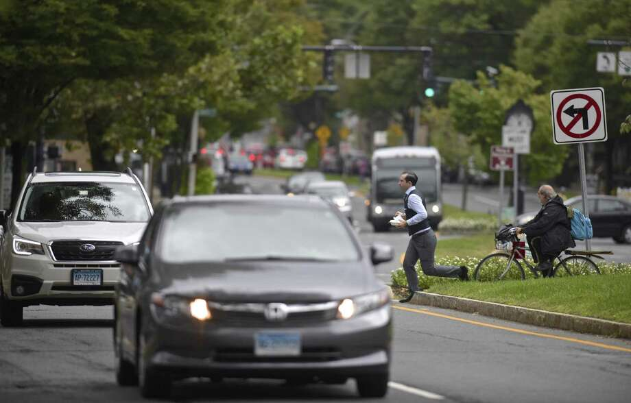 A pedestrian runs across Main Street at its intersection with Kennedy Ave. and Crosby St., one of worst areas in the city for pedestrian versus car accidents. Wednesday, September 26, 2018, in Danbury, Conn. Photo: H John Voorhees III / Hearst Connecticut Media / The News-Times