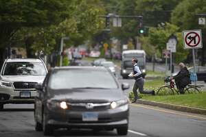 A pedestrian runs across Main Street at its intersection with Kennedy Ave. and Crosby St., one of worst areas in the city for pedestrian versus car accidents. Wednesday, September 26, 2018, in Danbury, Conn.