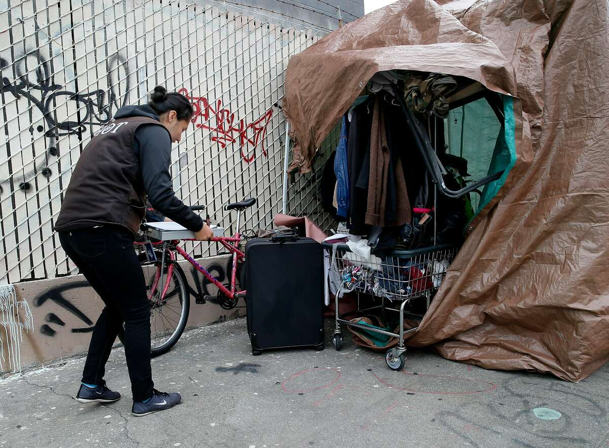 Hot team member Joanna Gobea helped a homeless woman with some paperwork as she cleared out of an encampment Monday April 20, 2015. A homeless encampment near the corner of 16th Street and Shotwell in San Francisco, Calif. was dismantled and the people moved to the new navigation center a few blocks away.