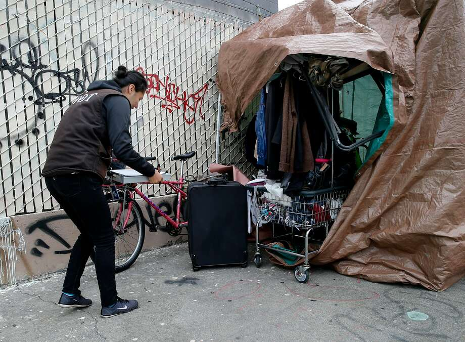 Hot team member Joanna Gobea helped a homeless woman with some paperwork as she cleared out of an encampment Monday April 20, 2015. A homeless encampment near the corner of 16th Street and Shotwell in San Francisco, Calif. was dismantled and the people moved to the new navigation center a few blocks away. Photo: Brant Ward, The Chronicle
