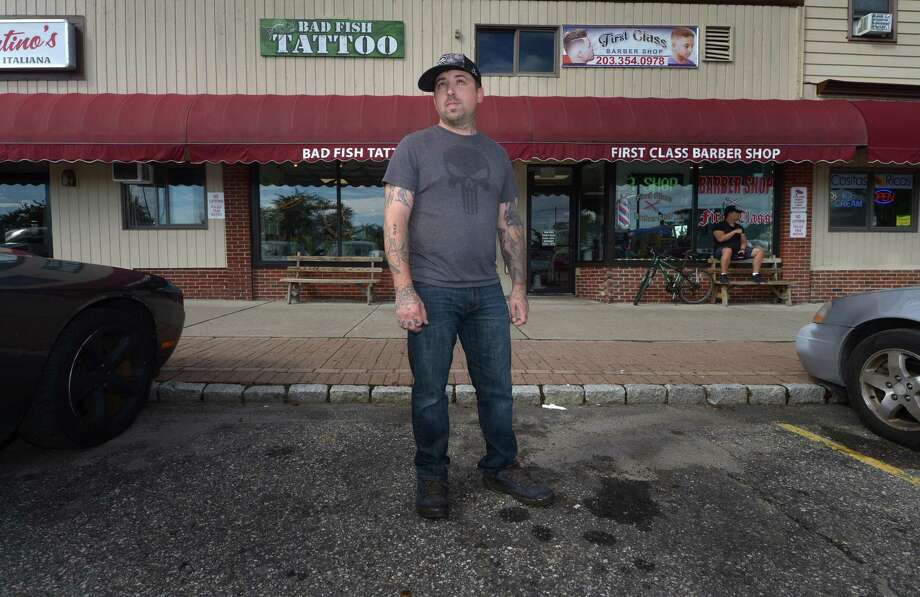 Anthony Neaves, owner of Bad Fish Tattoo, looks out onto the parking lot of Liberty Square that is renovated Thursday, September 27, 2018, in Norwalk, Conn. The Norwalk Parking Authority is establishing a management plan for the Liberty Square parking lots and inviting public comment on an ongoing citywide parking capacity study during their October meeting. Photo: Erik Trautmann / Hearst Connecticut Media / Norwalk Hour