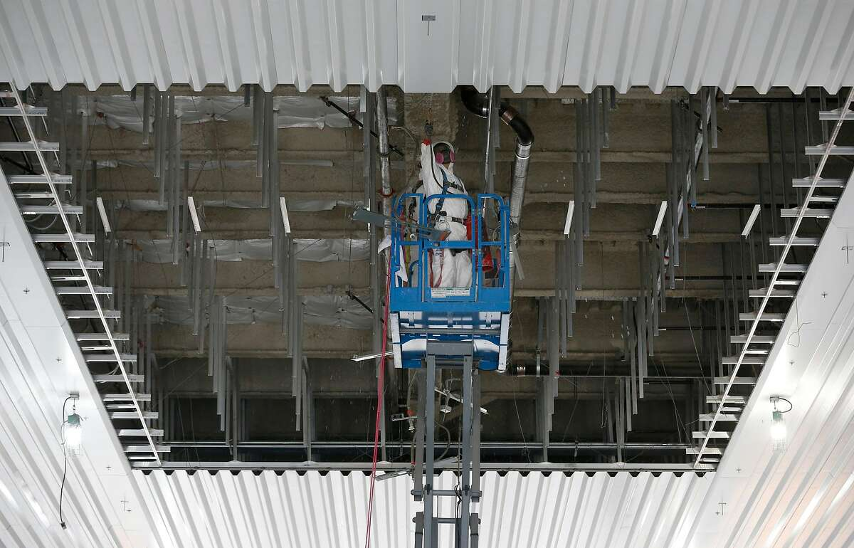 Men in hazmat suits prepare the underside of the Salesforce Transit Center above Fremont Street for a steel beam to be put in place in San Francisco, Calif. on Friday, Sept. 28, 2018. The beam will reinforce the structure while work to repair cracks discovered in two other beams can be repaired.