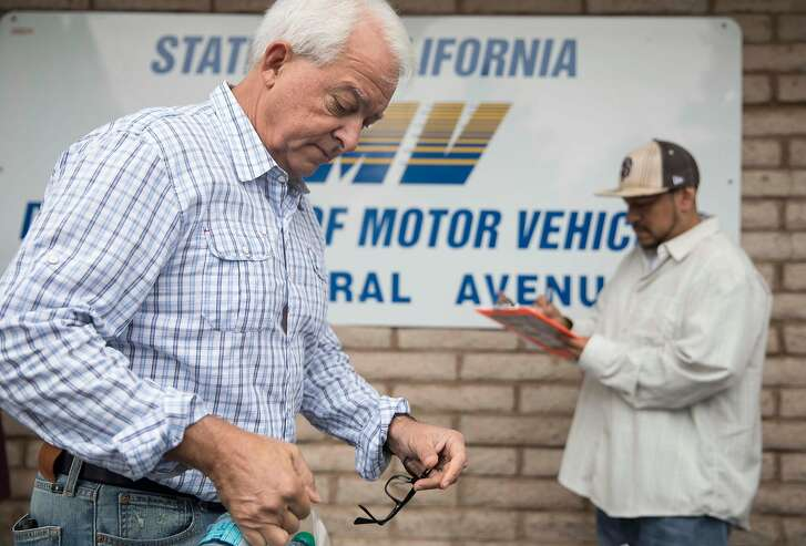 Republican Governor candidate John Cox hands out bottles of water to people in line during a stop on his state-wide tour at the Central Fremont DMV in Fremont, Calif. Friday, Sept. 28, 2018.