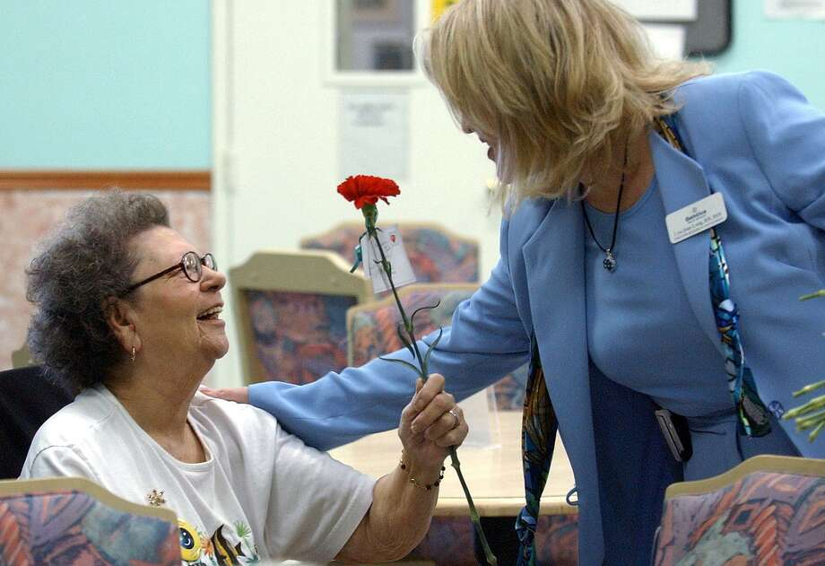 A resident at Trinity Care Services enjoys a Valentine's Day carnation in 2004. Until tort reform in 2003, Texas nursing home were threatened with closure because of rising liability insurance costs. Now they can spend more on improving quality of care, and hiring and retaining staff. Photo: Staff File Photo