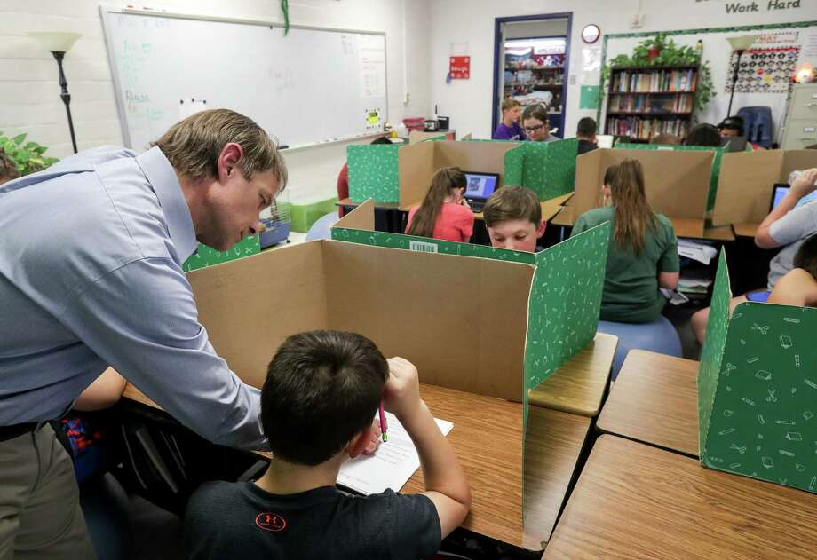 Steven Horelica, the mayor-elect of Devers, Texas, and the fifth grade teacher at Devers Elementary School, works with Kody Sandefer, 11, in his classroom, May 8. Adding school days will be costly, money that might be better spent on other measures to improve schools. Photo: Jon Shapley /Houston Chronicle / © 2018 Houston Chronicle