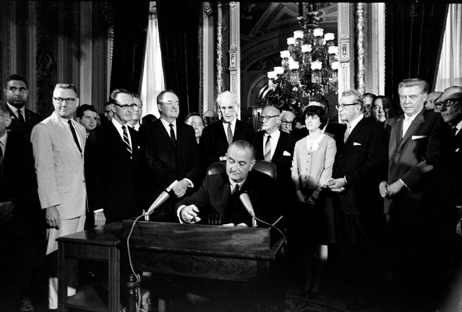 President Lyndon Johnson signs the Voting Rights Act of 1965. Today, there is an active effort to undo its protections. Photo: Associated Press File Photo / AP