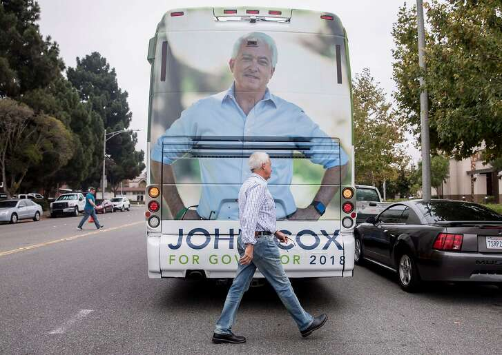 Republican Governor candidate John Cox returns to his campaign bus after a stop on his state-wide tour at the Central Fremont DMV in Fremont, Calif. Friday, Sept. 28, 2018.