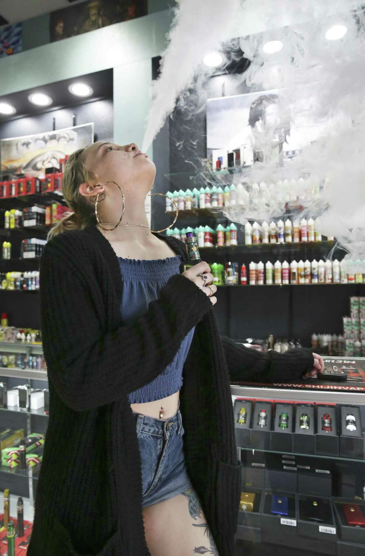 Employee Claire Collingwood exhales after using a vape at Hazel Sky Smoke and Vape #3 does business on September 27, 2018.
