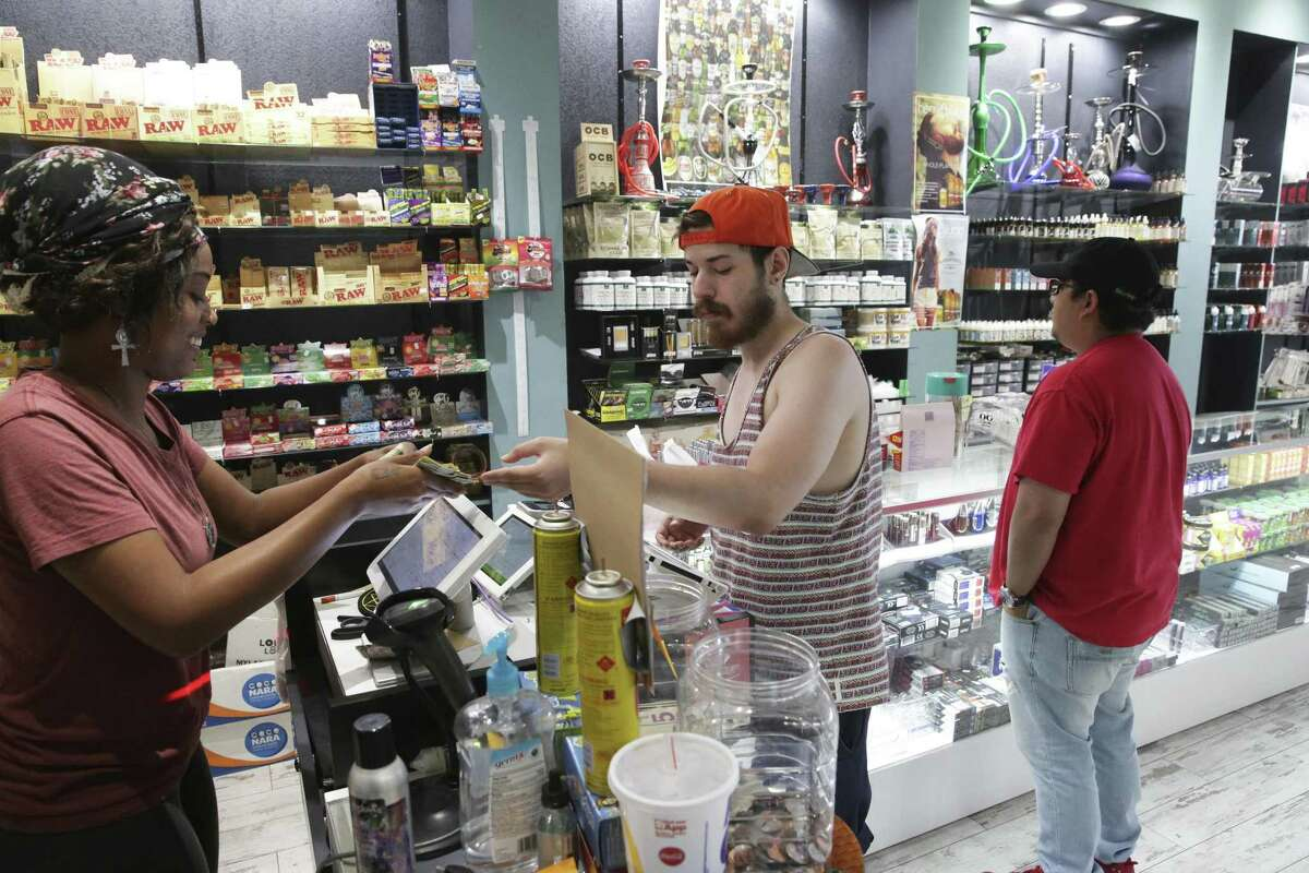 Employee Rem Smith helps Brandon Luna with a purchase at Hazel Sky Smoke and Vape #3 does business on September 27, 2018. In the background is Anthony Luna who was also shopping for smoking gear.