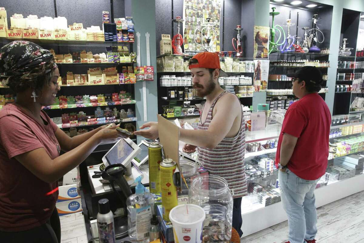 Employee Rem Smith helps Brandon Luna with a purchase at Hazel Sky Smoke and Vape #3 in September. Anthony Luna, in the background, is shopping for smoking gear.